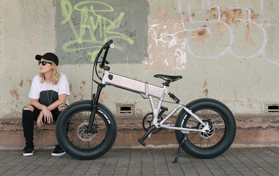 a woman sits in front of a graffiti walk with a bike next to her.