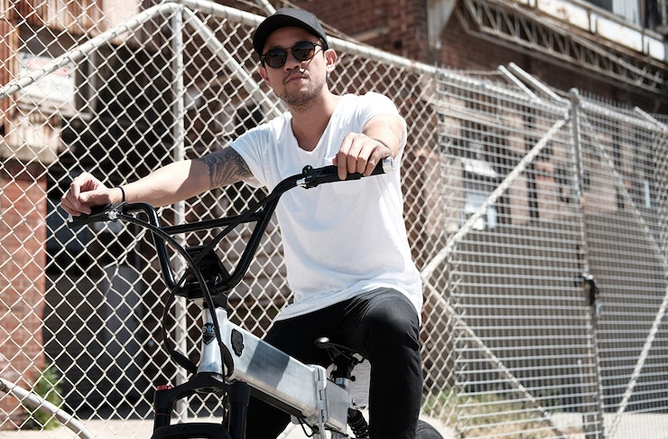a man rides a bike. behind him is a wire fence and industrial buildings.