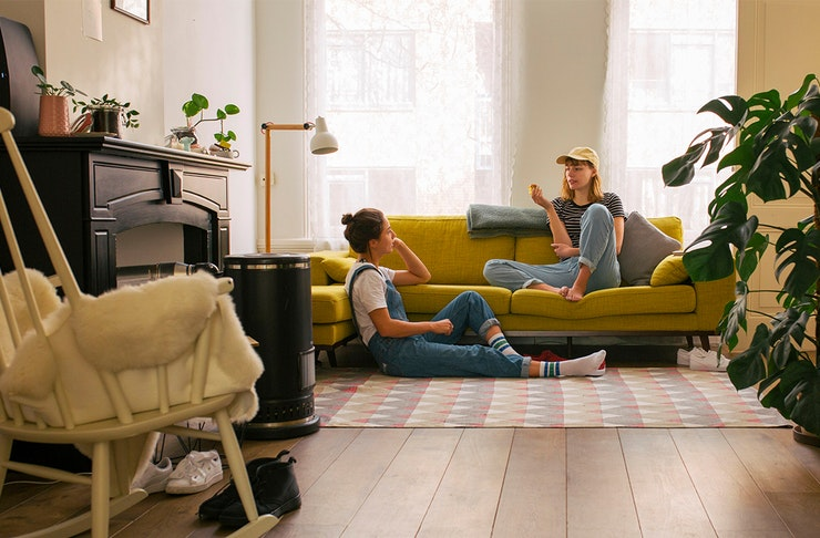 two women relax in a living room. one sits on a mustard couch while the other sits on the floor.