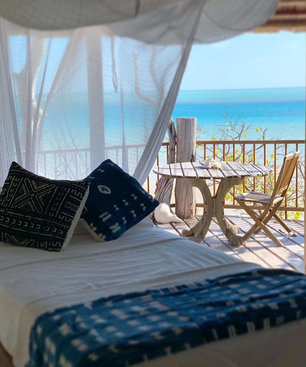 a bed lies inside a beach up, through the open window is a stunning blue sky and sea.