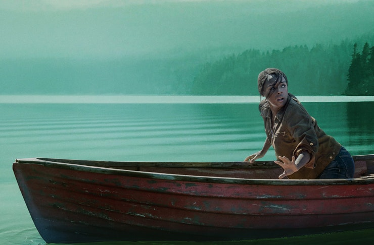 frightened woman in wooden row boat in the middle of misty lake