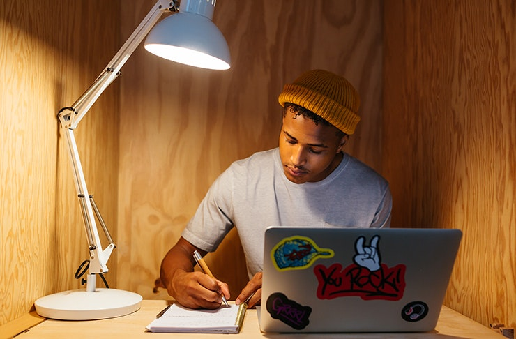 a man wearing a beanie sits at his desk writing in a notebook, in front of his is a lap top.