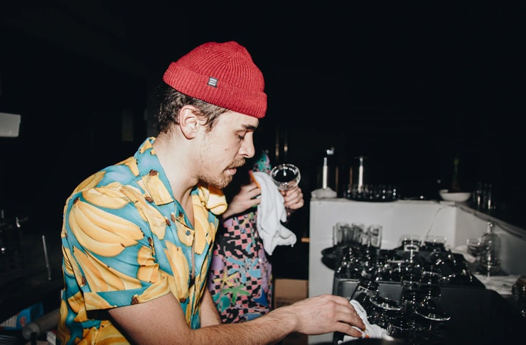 bartender at cleaning glasses behind bar wearing party shirt and  beanie