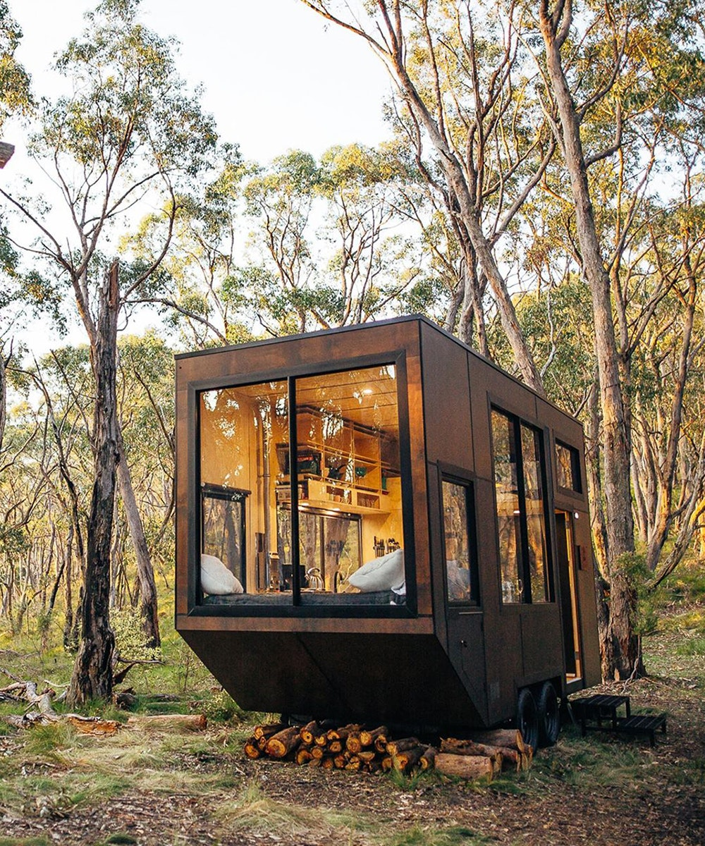 a free standing wooden cabin is nestled amongst the trees in the adelaide hills