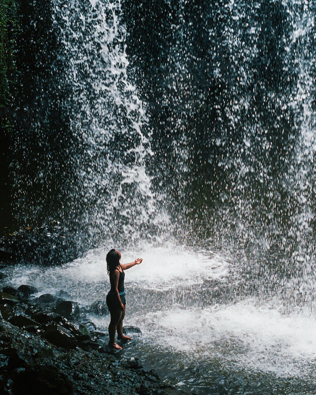 young girl in swimmers standing under killen falls near byron bay