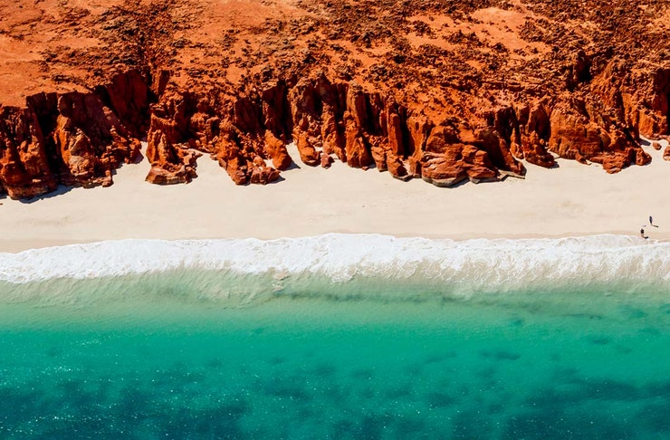 a sparkling blue ocean meets white sand that's fringed with a red rock coastline.