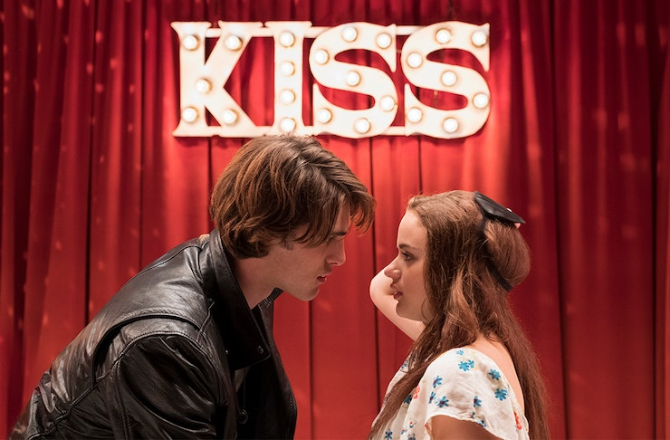 stars of the kissing booth movies Joey King and Jacob Elordi move in to kiss each other on set. Behind them is large red sign that reads Kiss on it.