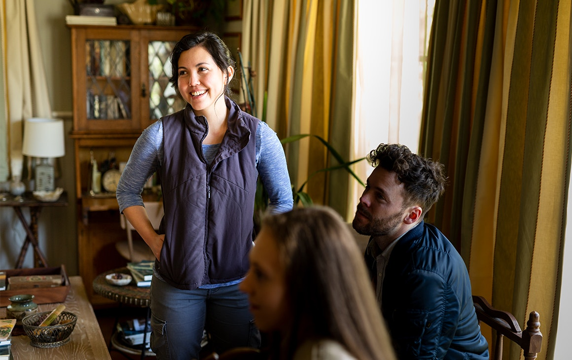 Director Natalie Erika James on set smiles while directing a man and a woman in a lounge room.