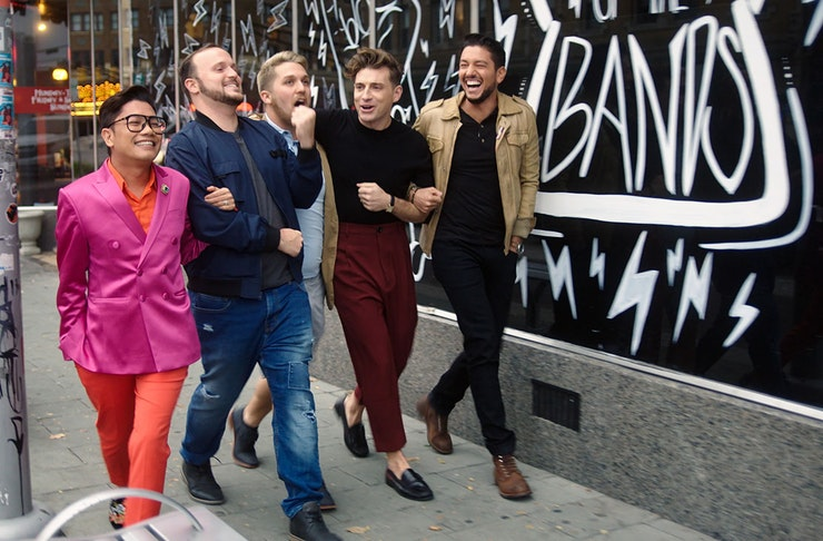 five men, link arms, walk down a busy street in the city, smiling.