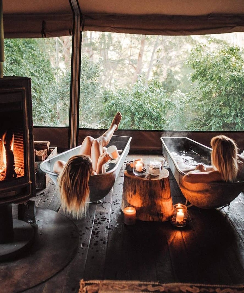 two woman sit in two tin bathtubs next to a fire. they're looking out at the green national park beyond.