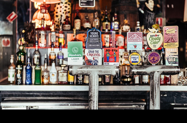front bar of sydney's iconic oxford tavern featuring beer taps and bottles of spirits