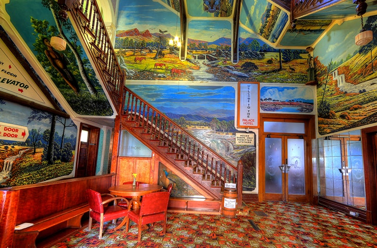 inside of palace hotel — foyer is painted completely in bright murals of australian outback