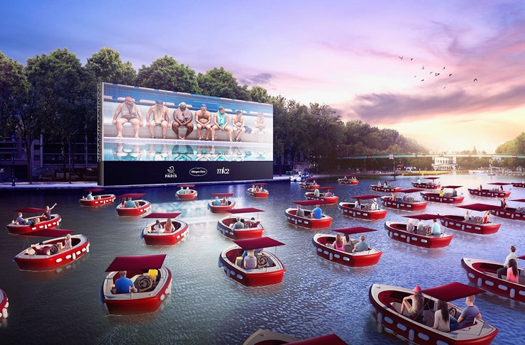 paris floating cinema on the canal with people in electric boats watching film outdoors