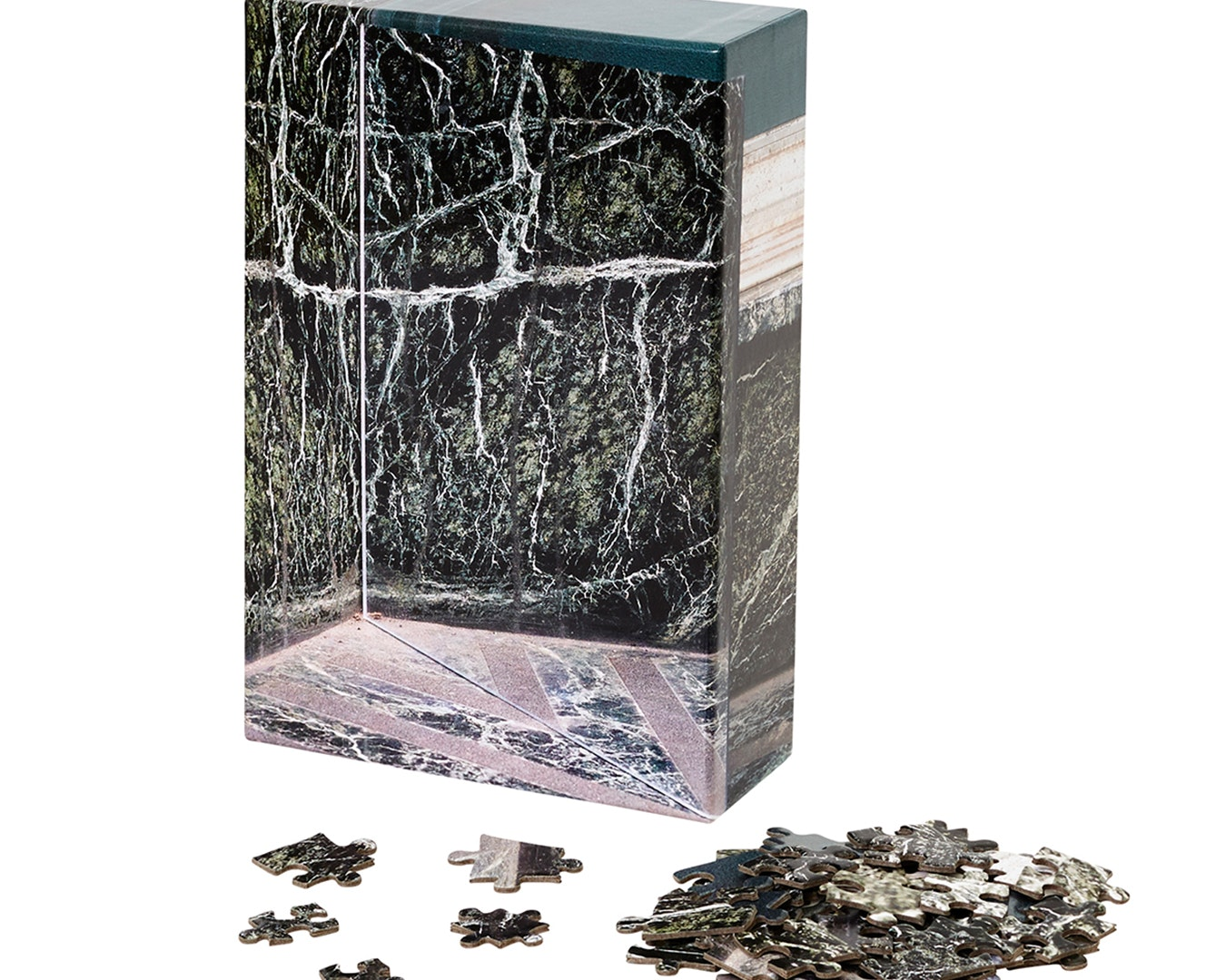 Puzzle box featuring grey, marble pattern. In front of it are a few single puzzle pieces.