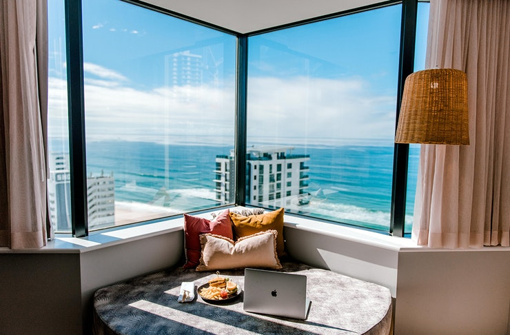 a stunning view of the blue sky and pristine gold coast beach is scene from a hotel room window.