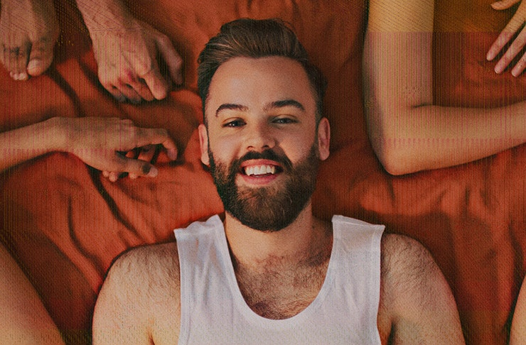 rowdie walden lying on bed sheet with arms framing him — host and creater of sex podcast search engine sex