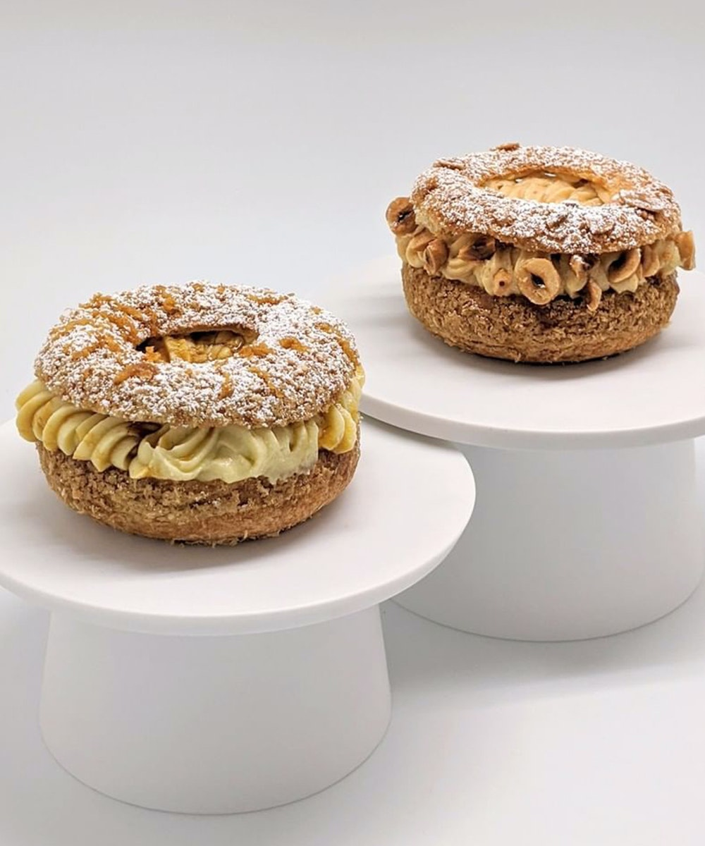 two delicate pastries sit on a white cake stand.