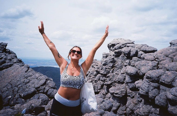 Sianna Catullo throws her arms up in the air with a blue sky before her.