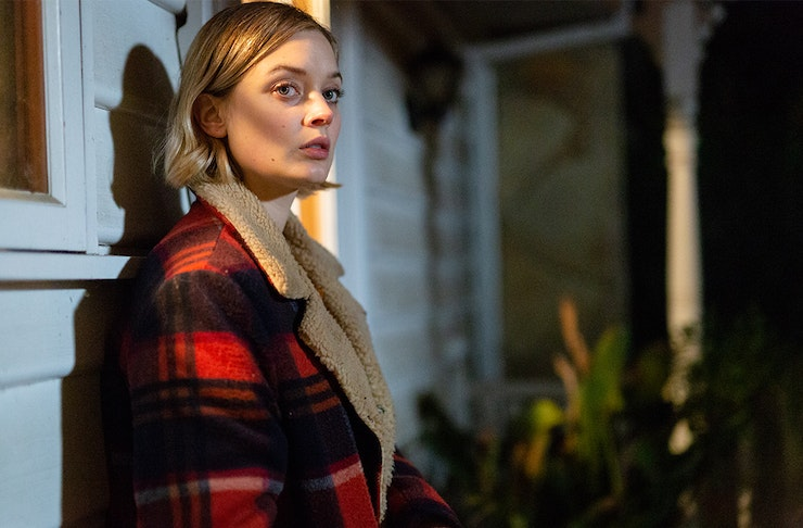 A young woman dressed in a warm coat leans against the outside of a house. In the background there's light peaking through a door.