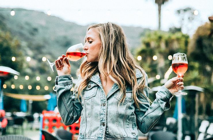 A woman holds a glass of red wine in each hand, she sips from one. Behind her are string of fairy lights and green mountains.