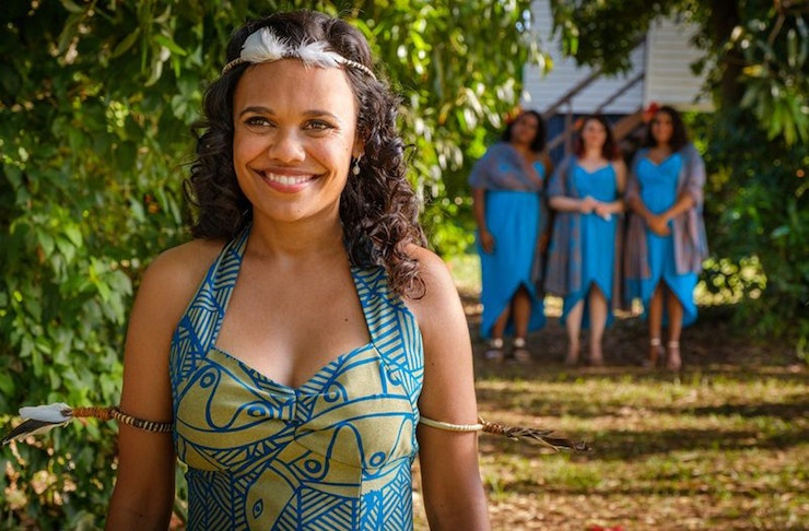 Miranda Tapsell is in character on the set of Top End Wedding. She's  wearing a colourful blue and green dress, while three women in blue dresses huddle behind her.