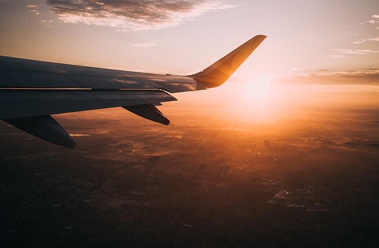wing of plane flying above urban sprawl at sunset set