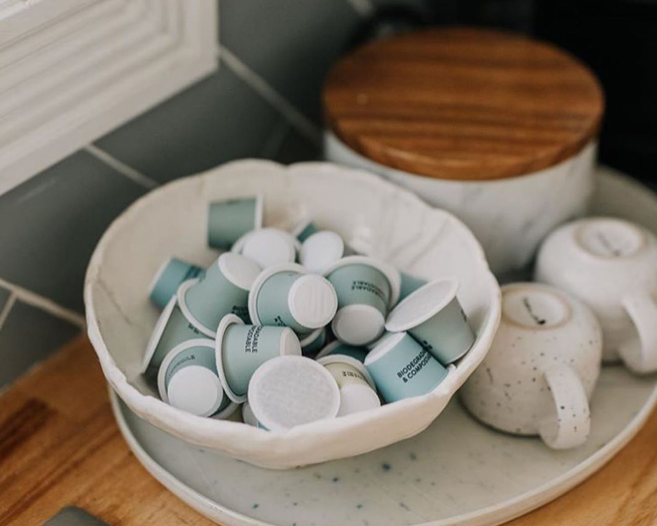a bunch of coffee pods in a bowl on a kitchen counter.