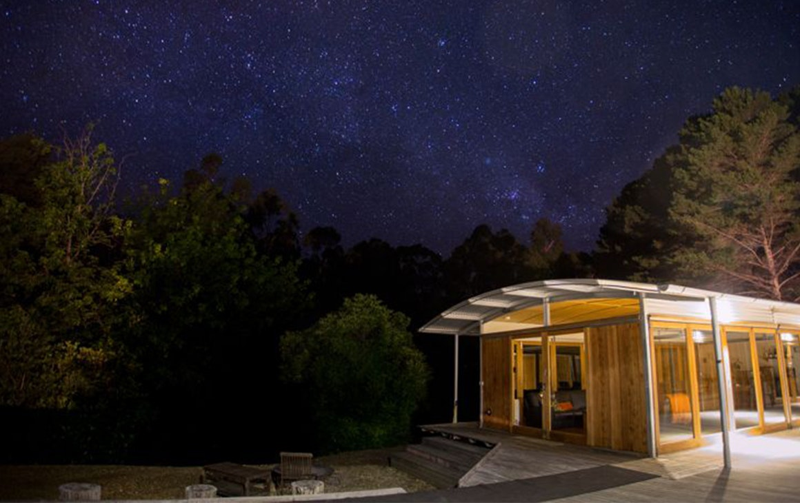 The beautiful Twelve Apostles Lodge at night, with a stunning view of stars above it.