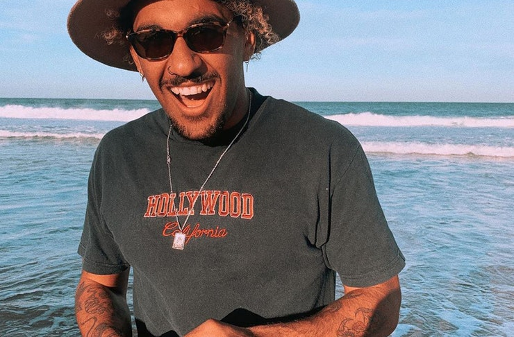 triple j presenter, Tyrone Pynor wears sunnies and a hat while laughing at the beach and the sun sets behind him.