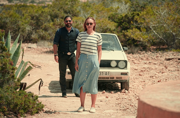 a woman, in a denim skirt and sunglasses, stands in front of an old white car on a dirt road. To the right is a man dressed in head to toe black.