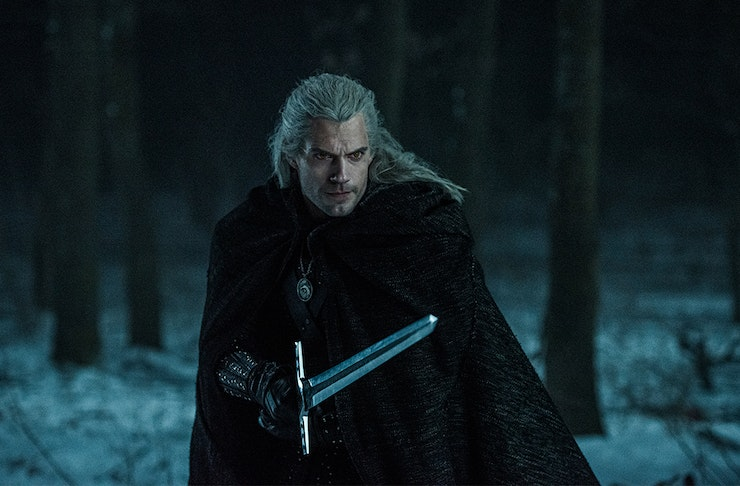 Geralt Of Rivea readies himself for a fight with a sword in his hands in the middle of a forest at night.