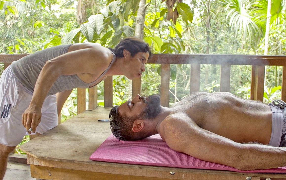 zac efron lies shirtless on a table in the jungle while a man blows smoke in his face.